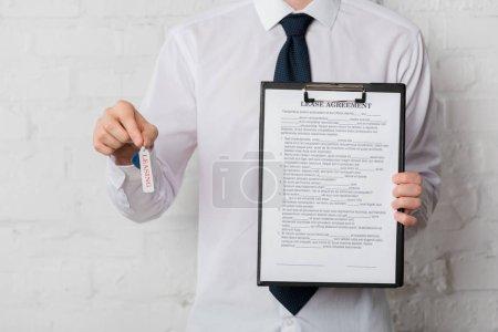 Photo pour Crochet vue de l'agent immobilier en costume tenant la clé et le presse-papiers avec le contrat de location sur blanc - image libre de droit