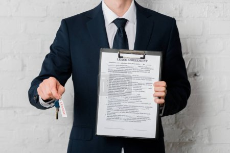 Photo for Cropped view of realtor in suit holding key with leasing lettering and clipboard with lease agreement on white - Royalty Free Image