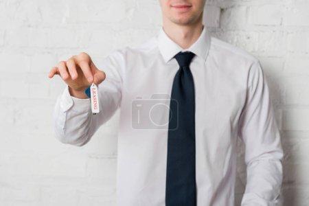Photo pour Vue recadrée de l'agent immobilier heureux en costume tenant clé avec lettrage de location sur blanc - image libre de droit