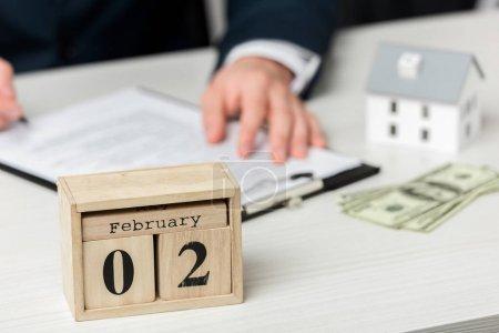 Photo pour Foyer sélectif du calendrier en bois avec lettrage février près de l'agent immobilier - image libre de droit
