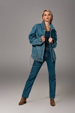 Photo pour Attractive woman in denim jacket and jeans looking at camera on grey background - image libre de droit