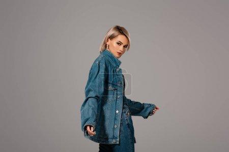 Photo pour Jolie femme en jean et veste en jean regardant la caméra isolée sur gris - image libre de droit