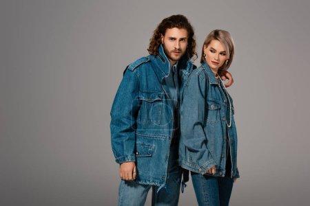 Photo pour Homme élégant serrant la femme dans une veste en denim isolée sur gris - image libre de droit