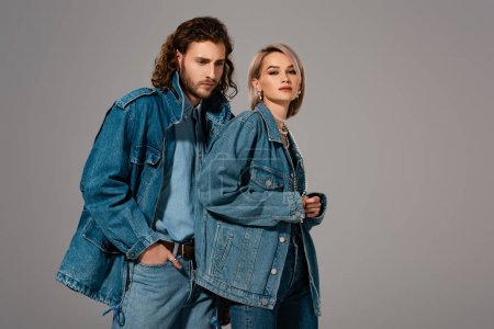 Photo pour Homme et femme stylisés en manteau en denim regardant la caméra isolée sur gris - image libre de droit