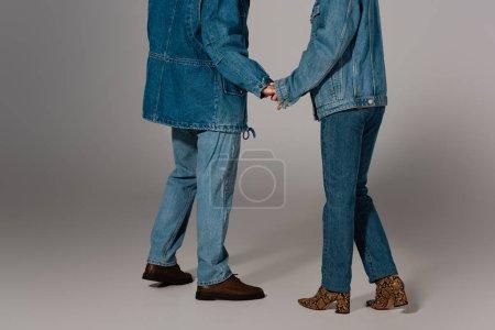 Photo pour Crochet vue d'un homme et d'une femme élégants vestons et jeans en denim tenant la main sur fond gris - image libre de droit