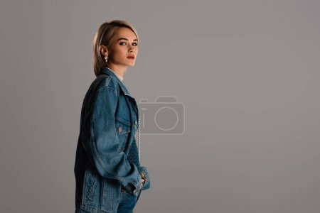 Photo pour Attractive woman in denim jacket with hand in pocket looking at camera isolated on grey - image libre de droit