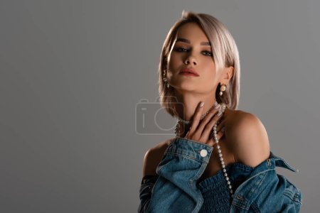 Photo pour Attractive woman in denim jacket looking at camera isolated on grey - image libre de droit