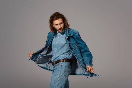 Photo pour Bel homme élégant vêtu d'une veste et d'un jean en denim, regardant loin isolé sur gris - image libre de droit