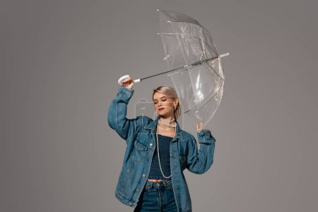 attractive woman in denim jacket holding umbrella isolated on grey