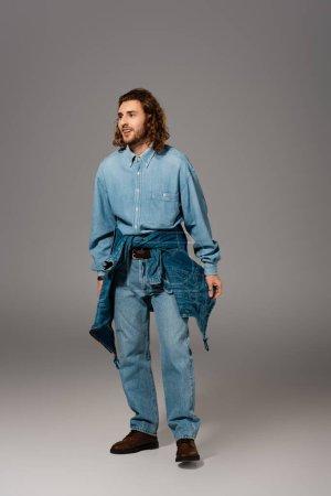 Photo pour Homme souriant en chemise et jeans en denim regardant loin sur fond gris - image libre de droit