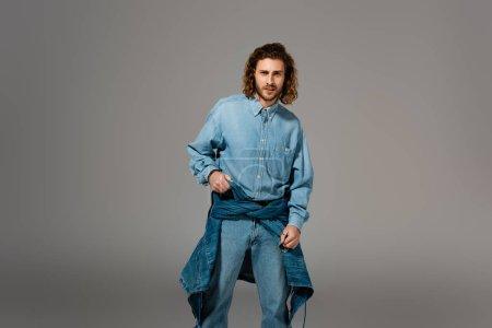 Photo pour Bel homme élégant en denim chemise et jeans regardant la caméra isolée sur gris - image libre de droit
