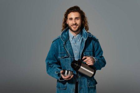 Photo pour Homme souriant et élégant veste en denim tenant thermos isolé sur gris - image libre de droit
