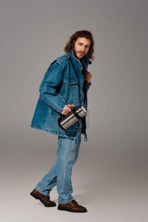 Photo pour Homme souriant veste en denim et jeans tenant thermos sur fond gris - image libre de droit