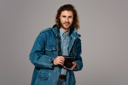 Photo pour Homme souriant veste en denim tenant appareil photo numérique isolé sur gris - image libre de droit