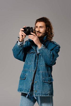 Photo pour Bel homme élégant en jean et veste en jean prenant des photos isolées sur gris - image libre de droit