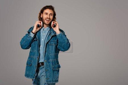 Photo pour Bel homme souriant veste en denim et jeans avec écouteurs isolés sur gris - image libre de droit