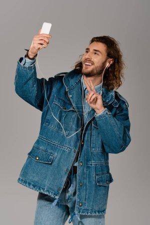 Photo pour Homme souriant veste en jean prendre selfie et montrant signe de paix isolé sur gris - image libre de droit