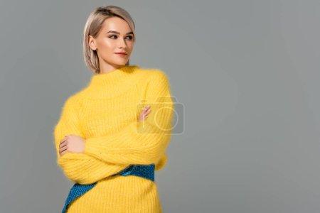 Photo pour Jolie femme en robe jaune aux bras croisés regardant loin isolée sur gris - image libre de droit