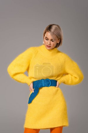 Photo for Attractive woman in yellow dress with hands on hips isolated on grey - Royalty Free Image