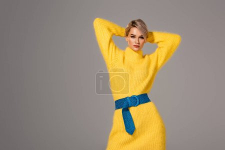 Photo pour Attractive woman in yellow dress looking at camera isolated on grey - image libre de droit