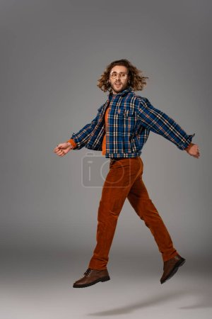 Photo for Handsome man in shirt and trousers jumping on grey background - Royalty Free Image