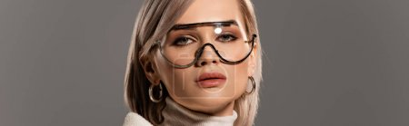 Photo for Panoramic shot of attractive woman in glasses and earrings looking at camera isolated on grey - Royalty Free Image