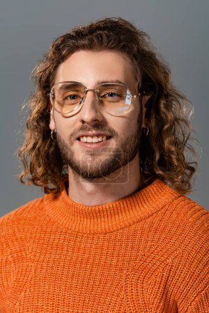 handsome and smiling man in orange sweater looking at camera isolated on grey