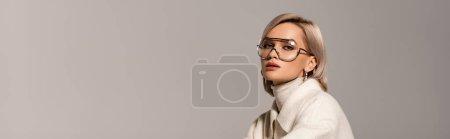 Photo pour Prise de vue panoramique d'une jolie femme en manteau et lunettes regardant la caméra isolée sur gris - image libre de droit