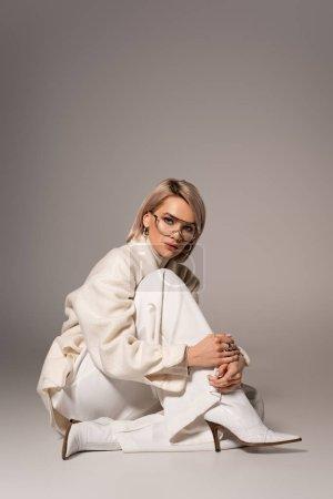 Photo pour Jolie femme en manteau blanc et pantalon assis sur fond gris - image libre de droit