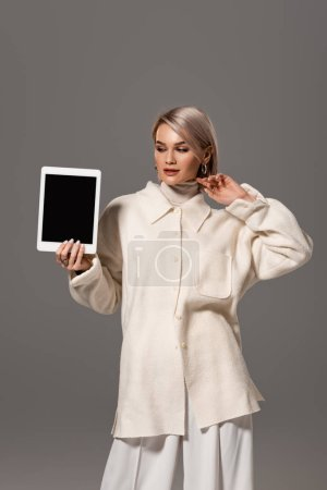 attractive and smiling woman in white coat holding digital tablet isolated on grey