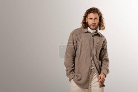 Photo pour Bel homme en chemise avec la main dans la poche en regardant la caméra sur fond gris - image libre de droit