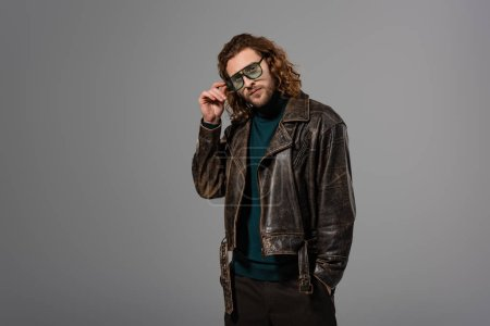 Photo for Handsome man in leather jacket touching glasses and looking at camera isolated on grey - Royalty Free Image