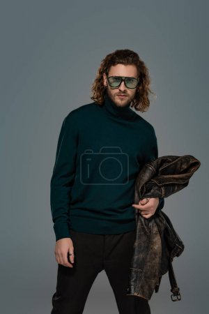 Photo for Handsome man in  turtleneck holding leather jacket isolated on grey - Royalty Free Image