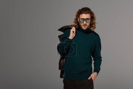 Photo pour Bel homme en col roulé tenant une veste de cuir isolée sur gris - image libre de droit