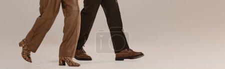 Photo pour Photo panoramique d'une femme et d'un homme en pantalon et en chaussure marchant sur fond gris - image libre de droit