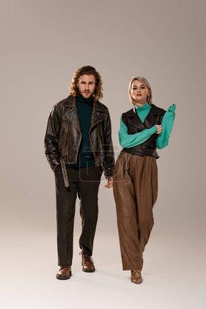 Photo pour Femme en gilet et homme en veste en cuir marchant sur fond gris - image libre de droit