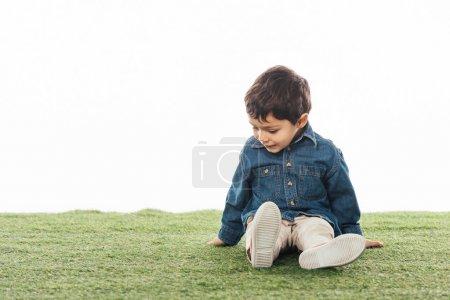 Photo pour Un garçon souriant et mignon assis sur de l'herbe isolé sur - image libre de droit