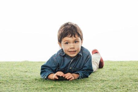 Photo pour Garçon mignon et souriant regardant loin et étendu sur l'herbe isolé sur blanc - image libre de droit