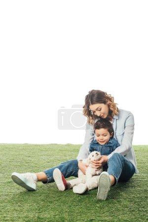 Foto de Sonriente madre e hijo mirando a la cachorra havanesa aislada en blanco. - Imagen libre de derechos