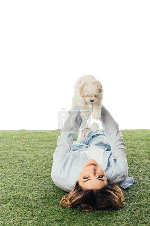 Photo pour Femme souriante couchée sur l'herbe et tenant chiot Havanais isolé sur blanc - image libre de droit