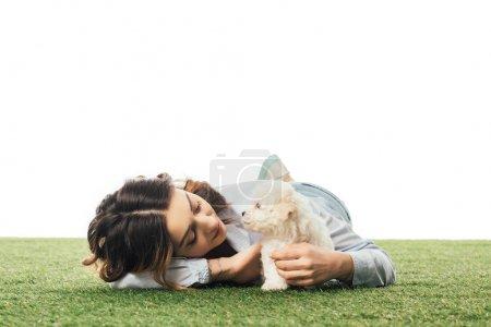 Photo pour Femme regardant chiot Havanais et couché sur l'herbe isolé sur blanc - image libre de droit