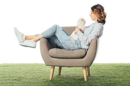 Photo pour Vue latérale de la femme tenant chiot Havanais et assis sur un fauteuil isolé sur blanc - image libre de droit