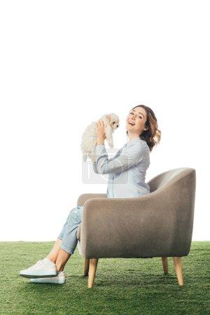 lächelnde Frau hält Havaneser Welpen und sitzt isoliert auf weißem Sessel