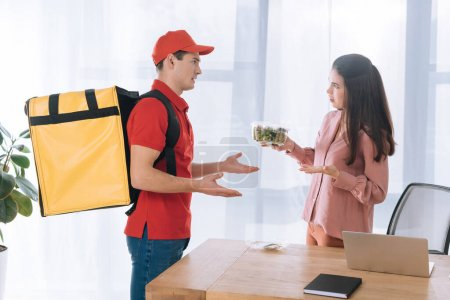 Photo for Side view of confused businesswoman with salad in container looking at courier with thermo backpack in office - Royalty Free Image
