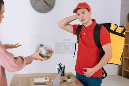 Photo for Angry businesswoman holding container with salad and looking at confused courier in office - Royalty Free Image