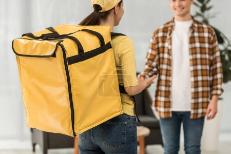 Photo for Selective focus of courier with thermo backpack standing near smiling man at home - Royalty Free Image