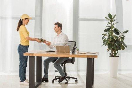 Photo pour Vue latérale du courrier donnant une salade à emporter à un homme d'affaires souriant à table au bureau - image libre de droit