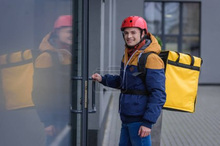 Photo pour Side view of courier with thermo backpack smiling at camera while opening door of building - image libre de droit