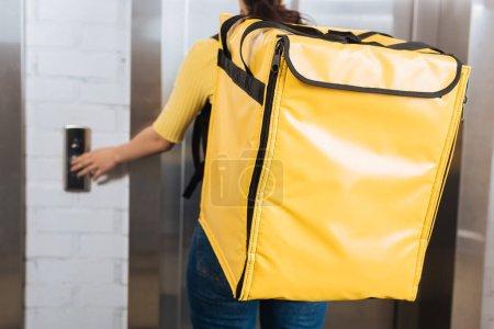 Photo pour Mise au point sélective du courrier avec thermo sac à dos appuyant sur le bouton d'ascenseur - image libre de droit