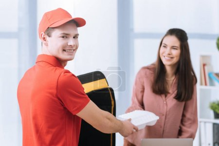 Photo for Selective focus of smiling courier looking at camera and giving takeaway box to smiling businesswoman in office - Royalty Free Image